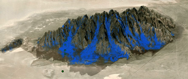 Figure 3. view of downslope flow on the east side of granite mountain during the evening transition. blue isosurfaces are shown for downslope velocity. the locations of observational towers are shown as green dots. (figure from arthur et al., 2016).