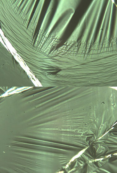 Figure 3. two films after plastic deformation. a film that has yielded by crazing is shown on the top. the dark lines are cracks in the material that are bridged by many tiny filaments of aligned polymer strands. a film that has yielded by shear-thinning is shown at the bottom. the material has become thinner, but shows no spatial anisotropy.