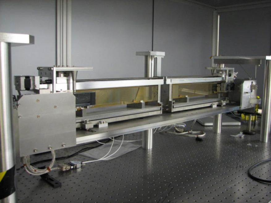 The multilayer delay line for x rays to be used for high-intensity, all-x-ray pump-and-probe experiments. the assembly is suspended from a support structure via six stainless-steel wires for thermal and vibrational stability. the fused silica glass rails (yellow rectangular bars) provide a smooth surface on top of which the silicon x-ray mirrors can slide with nearly wobble-free motion. the relative position of the mirrors determines the delay between the pump and the probe, and the minimized motion reduces